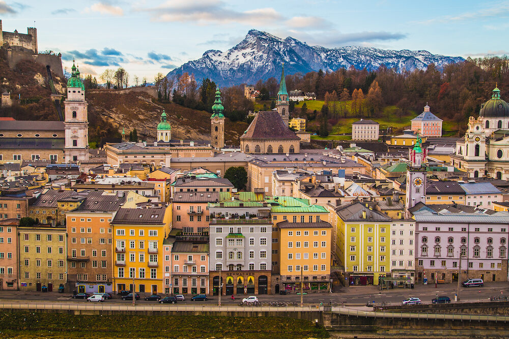 SALZBURG AUSTRIA : A high view of buildings and churches in Salzburg during the day showing the colourful exteriors. Mountains can be seen in the distance.