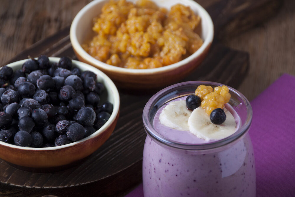Smoothies of cloudberries, a banana and a blueberry on a lilac napkin and blueberries and cloudberries in the background