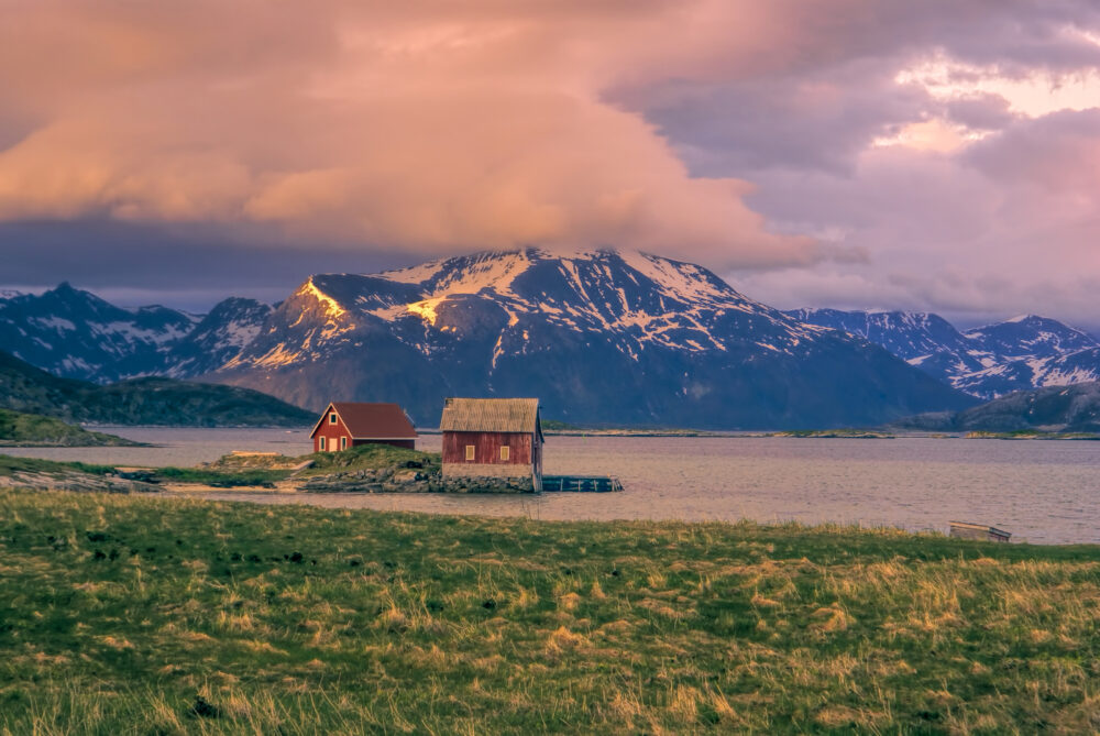 Picturesque view of two red wooden houses standing on the shore on Sommaroy
