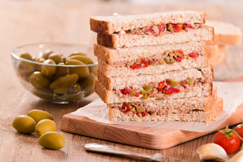 Tuna olives and tomato sandwiches on cuttingboard.