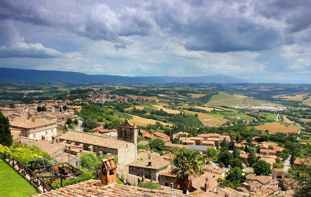 Panoramic view over old traditional houses in the green fields of the town Todi, Umbria, Italy.