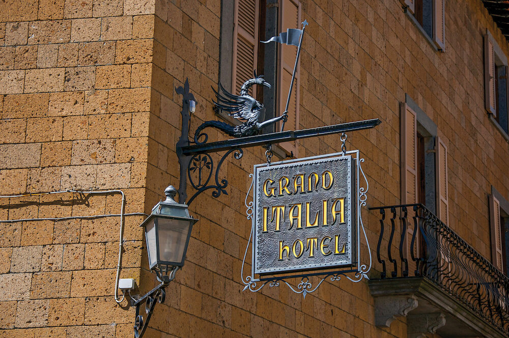 Orvieto, Italy - Close-up of elaborate Hotel plate, made of iron, stuck in stone wall and lamp in Orvieto, a pleasant and well preserved medieval town. Located in Umbria, central Italy