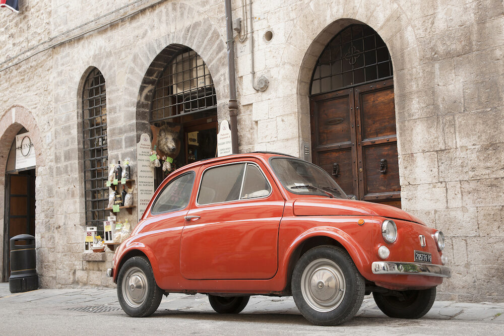 GUBBIO, ITALY - Iconic Italian orange Fiat 500 parked in Gubbio, Italy. The classic small car stands out in the historic walled hillside village.