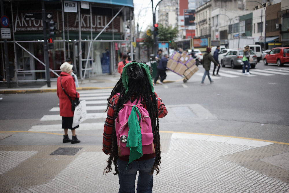 BUENOS AIRES, ARGENTINA - Unidentified woman walking through Avenida Corrientes with a backpack in Buenos Aires, Argentina