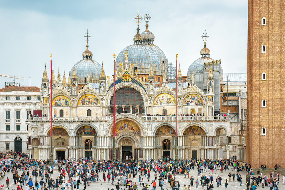 Venice, Italy - Basilica di San Marco or St Mark`s Basilica in Venice. It is a top tourist attraction of Venice. Lot of people walk near the old famous landmark in the Venice center.