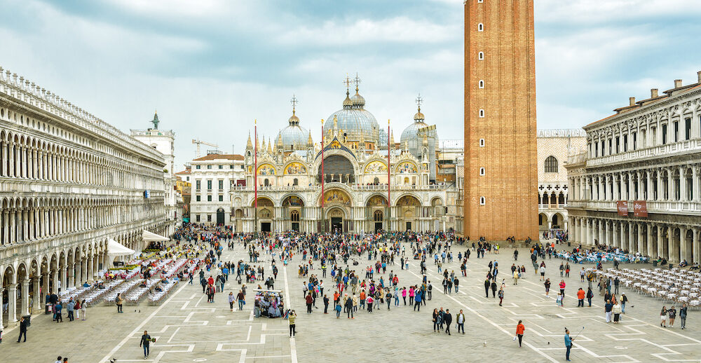 Venice, Italy - Piazza San Marco or St Mark`s Square in Venice. It is a top tourist attraction of Venice. Panoramic view of the famous Venice center in summer. People walk near Basilica.