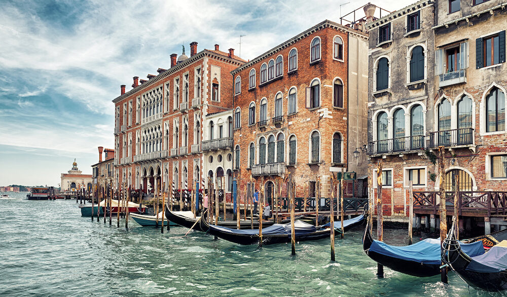 Traditional view of a street in Venice, Italy. Panorama of Venice with vintage buildings. Old houses on the famous Grand Canal in Venice. Historical architecture and cityscape of Venice in summer.