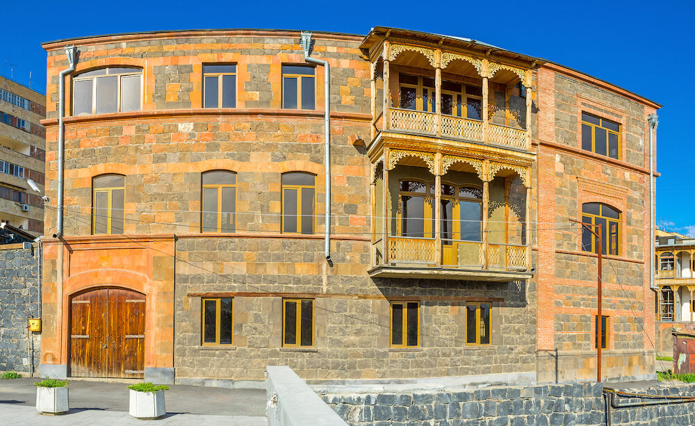 The fine example of traditional Armenian architecture house built of colorful stone bricks with the carved wooden balcony Yerevan.