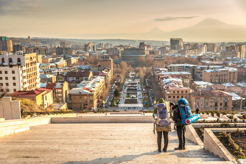 Yerevan, Armenia - - A couple of backpackers enjoying the sunset at the top of the Cascade with Yerevan city and a mountain in the background