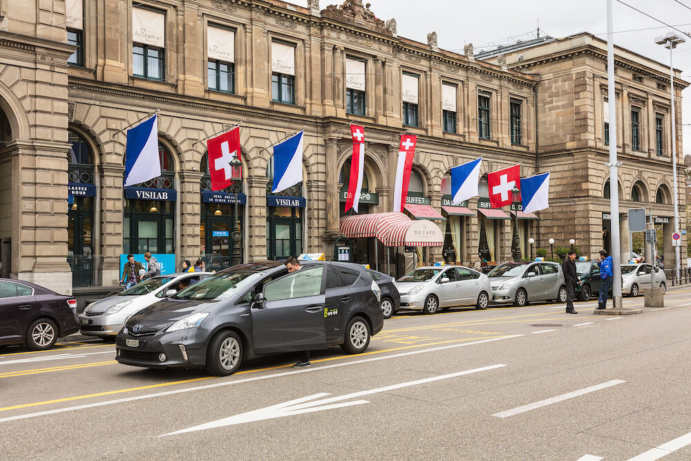 Zurich, Switzerland - part of the facade of the Zurich main railway station building, cars and people in front of it. Zurich main station is the largest railway station in Switzerland.