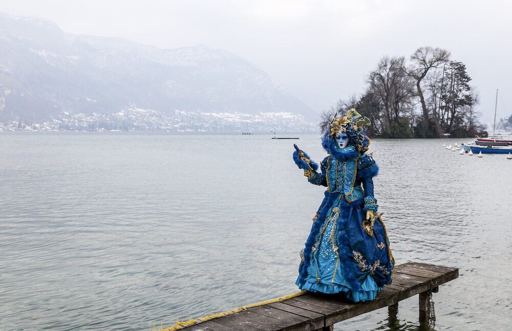 Annecy, France, Disguised person posing on a pier on Annecy Lake, during a Venetian Carnival which celebrates the beauty of the real Venice.