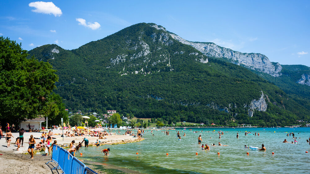 Annecy France, People enjoying the sunny summer day at Albigny beach and swimming in Annecy lake with Alps mountains in background in France