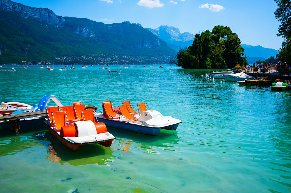 Scenic view of Annecy lake and pedalo with swan island in background in France during sunny summer day
