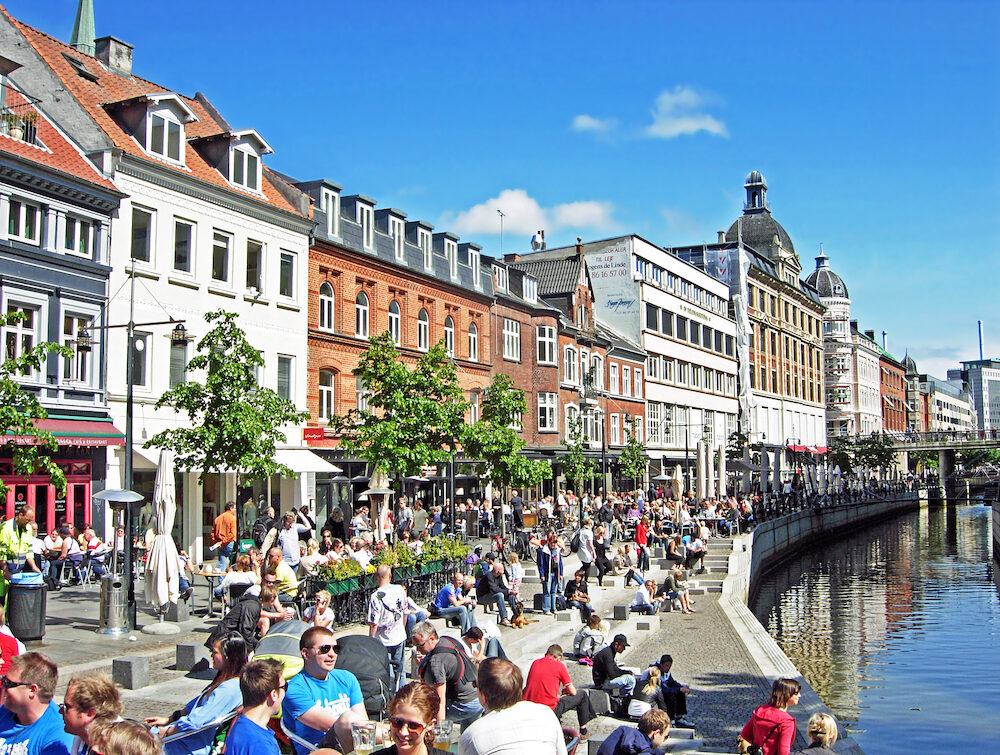 Aarhus, Denmark - Many people enjoying a sunny day at Aboulevard, the promenade along the river Aarhus A. Aarhus is located in the region Midtjylland and with about 260,000 inhabitants, the second largest city in Denmark.