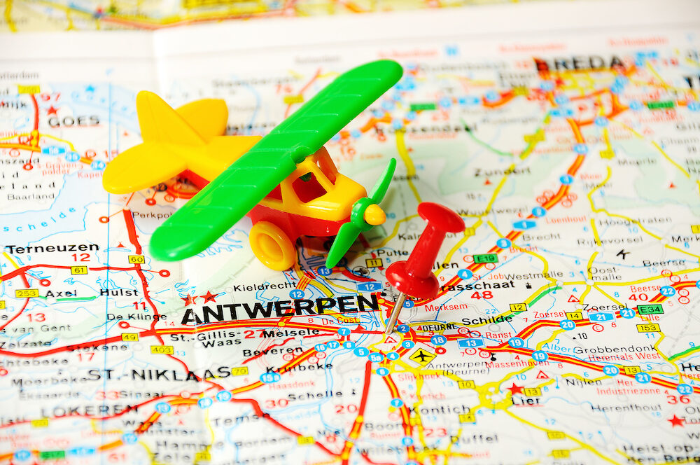 Red push pin pointing at Antverpen Belgium map and a airplane