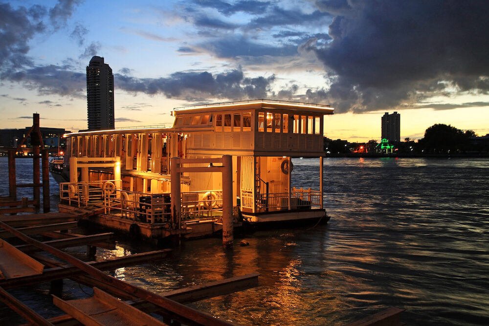 Boat dinner tour on Chao Phraya river at twilight in Bangkok Thailand