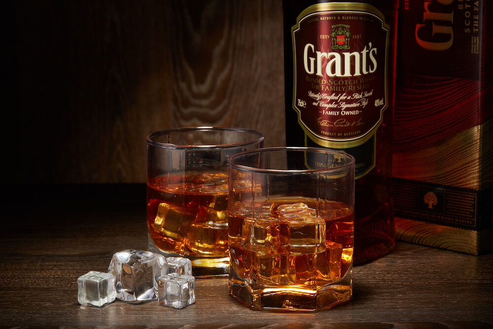 Bottle of Grant's whisky and two glasses with whisky and ices standing on a table on a dark wooden background with copy space.