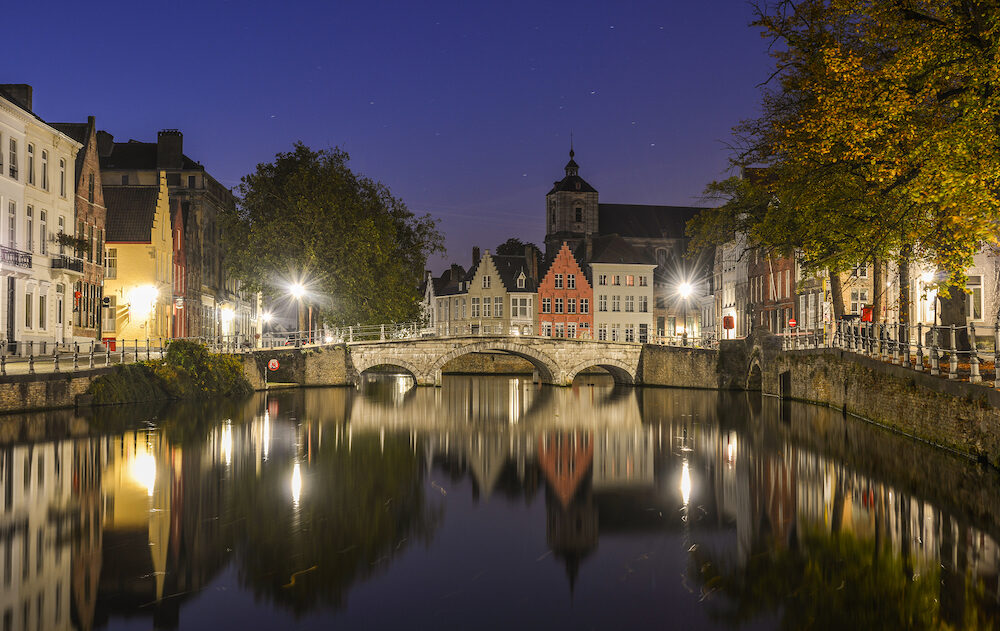 Scenic city view of Bruges canal with beautiful medieval colored houses at night in Bruges, Belgium.