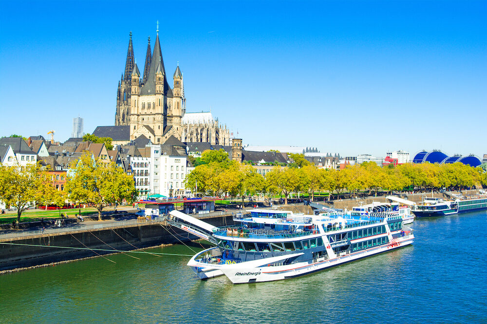 Cologne, Germany - Landscape of the waterfront of Rhine River with cruise ship and famous landmark - Cologne Cathedral and St. Martins Church