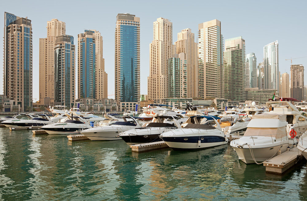 Luxurious Yachts and Boats in Front of Dubai Marina Skyscrapers in the daylight.