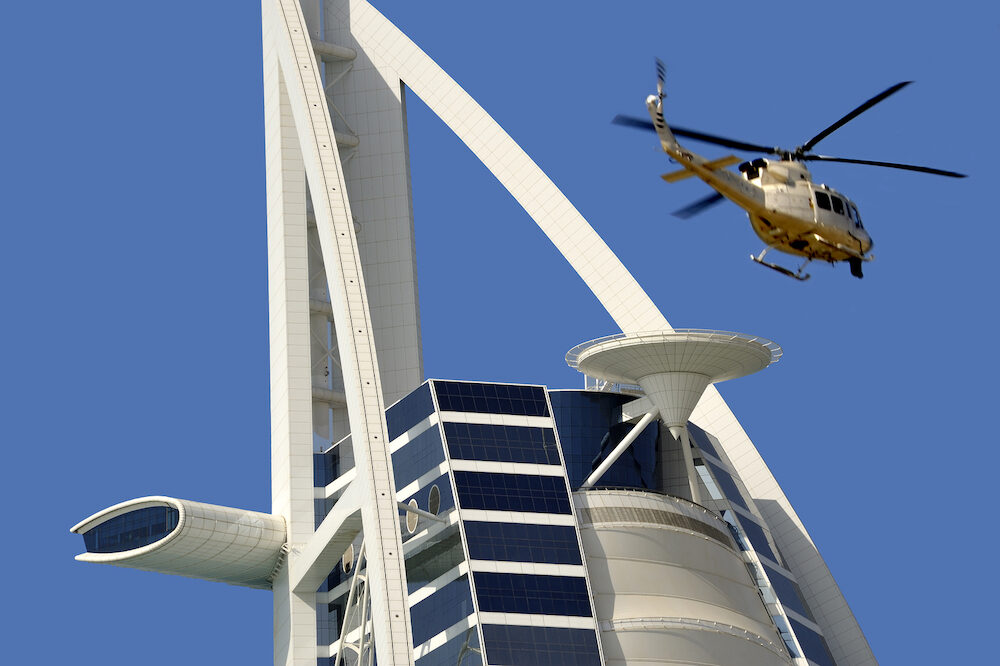Dubai United Arab Emirates - View of Burj Al Arab hotel with leaving helicopter from helicopter deck. Burj Al Arab is one of the Dubai landmark and one of the world's most luxurious hotels with 7 stars.