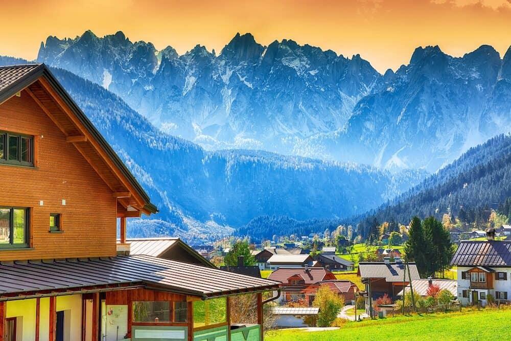 Alpine green fields and traditional wooden houses view of the Gosau village at autumn sunny day. Location: resort village Gosau Salzkammergut region, Gosau Valley in Upper Austria, Alps. Europe.