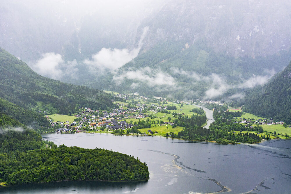 Rain and clouds on the Obertraun in Austria. Morning mist over the Austrian landscape with lake Hallstattersee, forests, fields, pastures and meadows