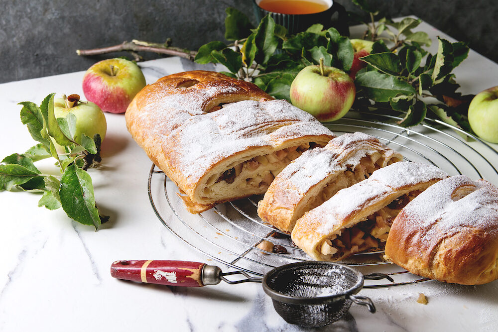 Homemade sliced puff pastry apple strudel pie on cooling rack served with ripe fresh apples, branches, cieve and sugar powder over white marble texture background.