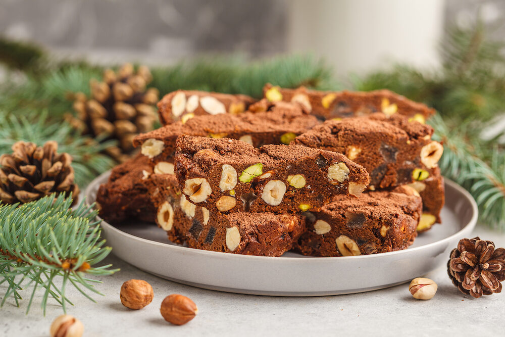 Italian Christmas dessert panforte with nuts, chocolate and candied fruits. Christmas background, Christmas dessert concept.