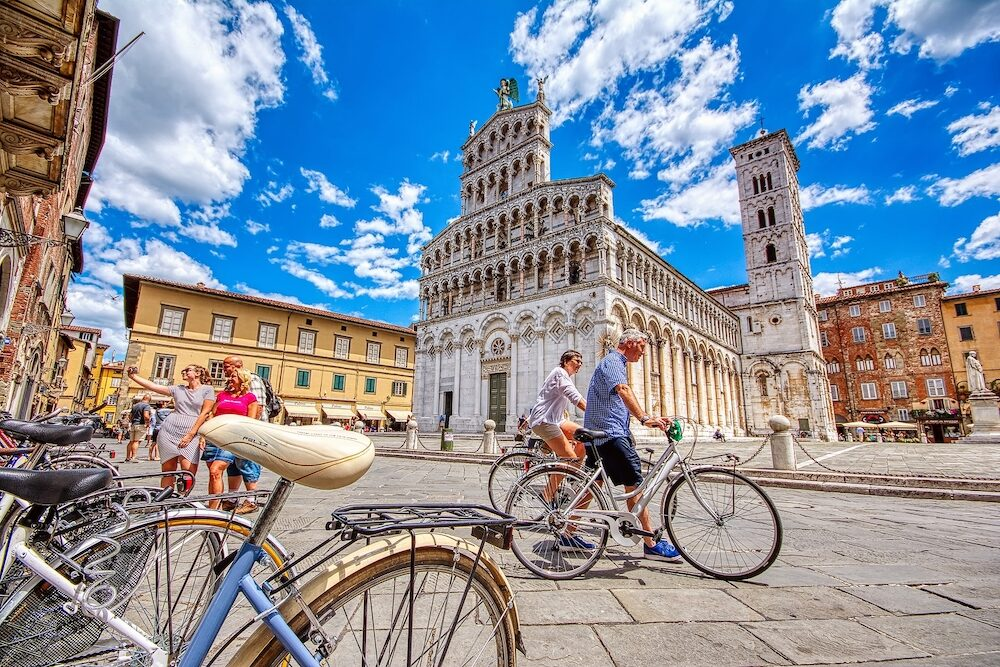 Lucca, Italy - View of medieval cathedral San Michele in Lucca, Italy. Tourists walking and cycling through the historic center of Lucca.