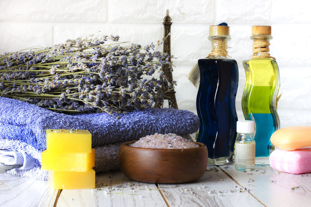 Natural lavender soap and bath salt, French oil and towels on white wooden background