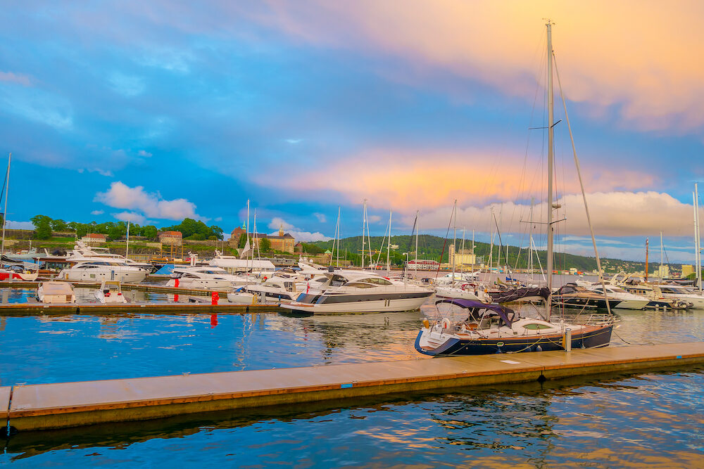 OSLO, NORWAY - Marina showing many boats of different kinds parked by Aker Brygge during sunset hour.