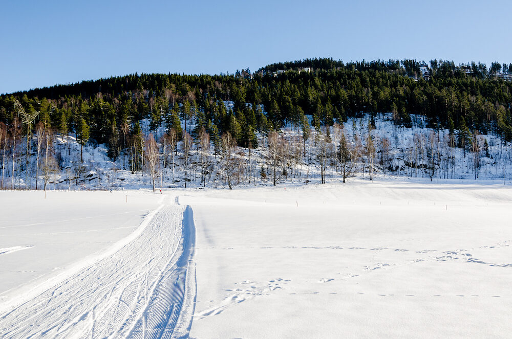 Road path and ski tracks on the frozen lake of Bogstadvannet in Oslo, Norway. Inspirational peace
