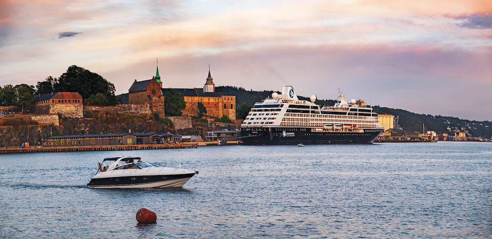 Oslo, Norway - View on Oslo Fjord harbor and Akershus Fortress at sunset, waterfront with large cruise ship in the port, Oslo, Norway