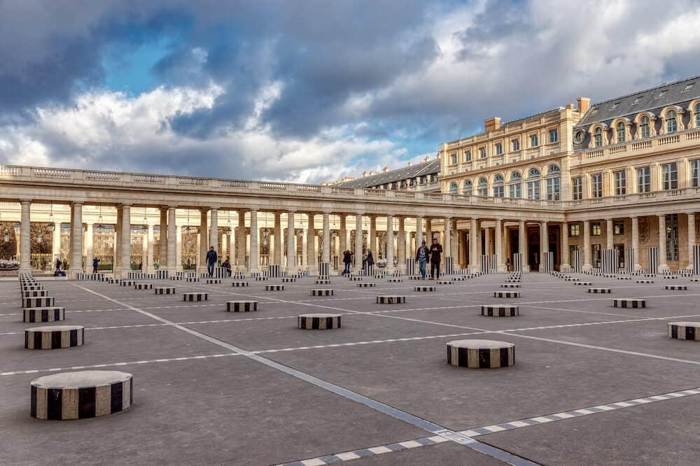 Paris, France - People walking in winter between the Buren columns in Cour dHonneur of the Palais Royal - Paris, France
