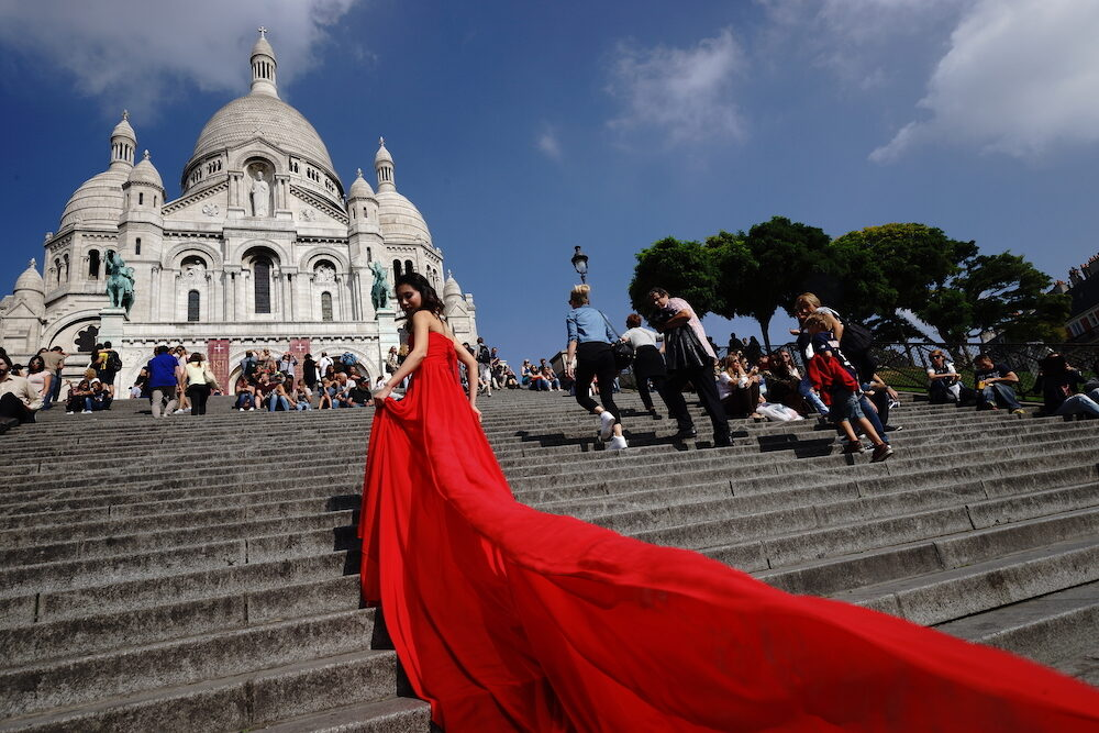 PARIS -model posing in red dress for photographer near Basilica of the Sacred Heart in Paris, France. Paris, aka City of Love, is a popular travel destination.