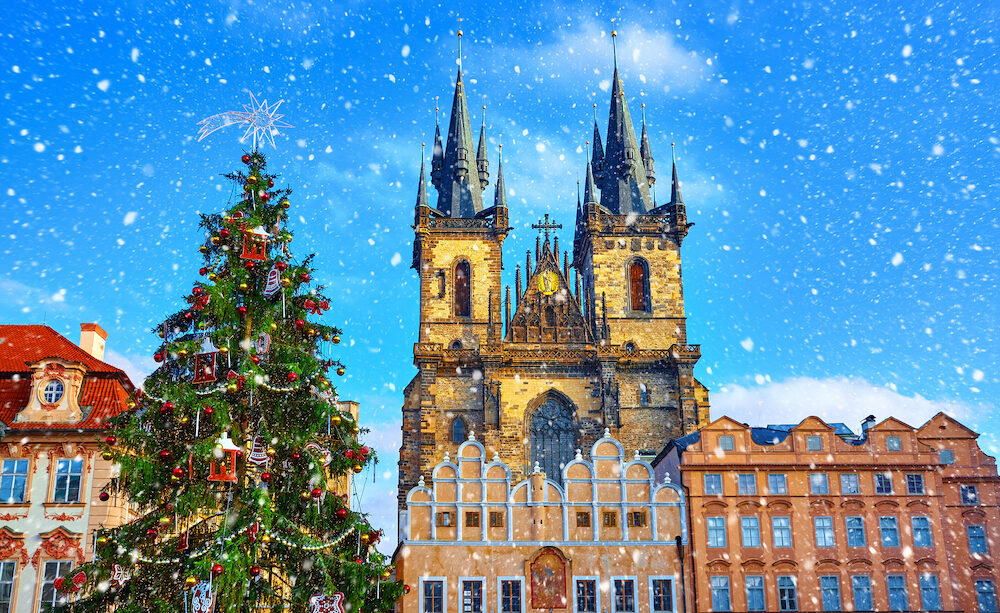 Christmas in Prague, Czech Republic. Green christmas tree at central square old town (Staromestska) in front of Church of Our Lady Before Tyn. Snowfall, snow in sunny holiday winter day.