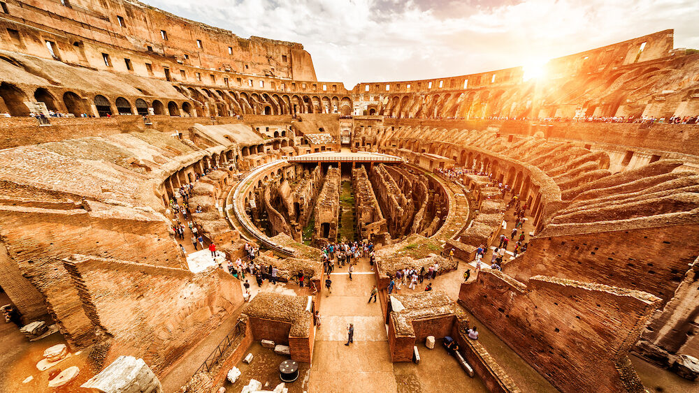 Rome, Italy - Inside the Colosseum or Coliseum in summer. Colosseum is the main travel attraction of Roma. Tourists visit the Colosseum. Panoramic view of Colosseum in the sunlight.