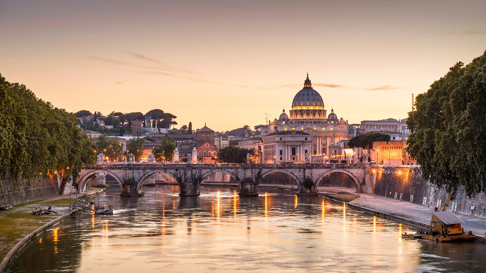 Rome at night, Italy. Sant`Angelo bridge and St Peter's Basilica. Rome landmark. Saint Peter's Basilica (San Pietro) is one of main travel attractions of Rome. Scenic night view of Rome and Vatican.
