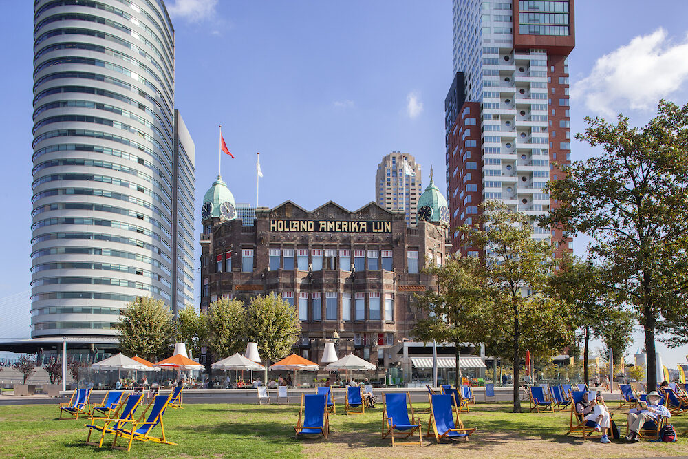 Rotterdam, Netherlands - Reading a book in a beach chair in front of the famous Hotel New York in Rotterdam