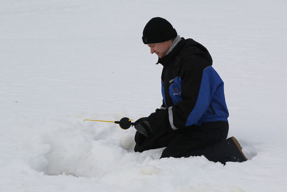 ROVANIEMI, FINLAND - fisherman during ice fishing on the frozen lake in Lapland, Finland