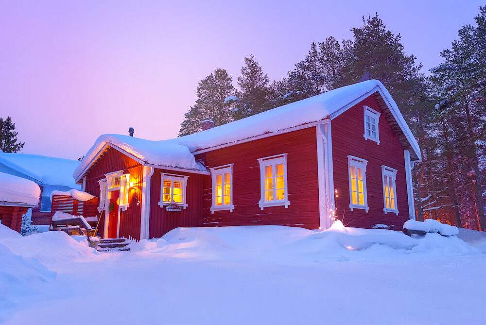 Wooden cottage Finnish house covered with snow in winter