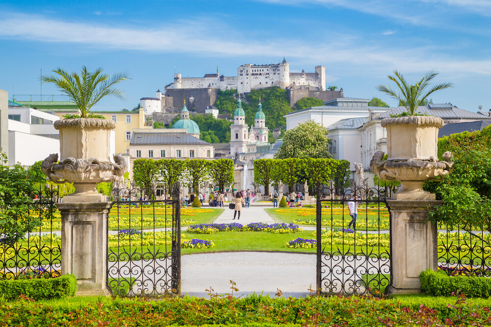 Classic view of famous Mirabell Gardens with the old historic Fortress Hohensalzburg in the background on a beautiful sunny day with blue sky and clouds in summer in Salzburg Austria