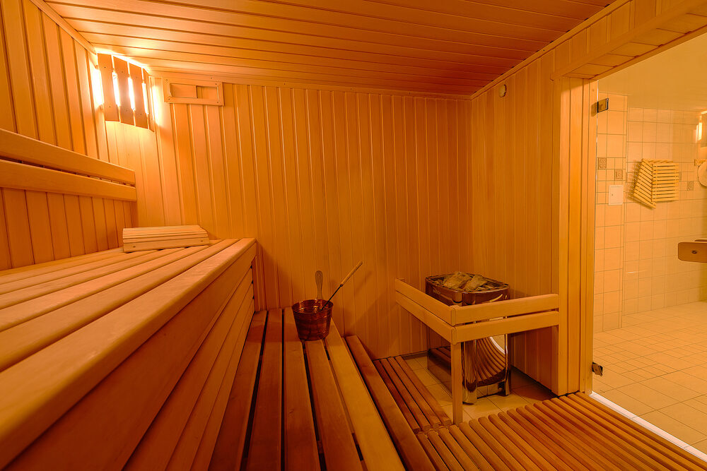 Sauna room interior as background, spa room. Relax in a hot sauna, Finland-style classic wooden sauna interior in public building, hotel. Small home Finnish wooden sauna
