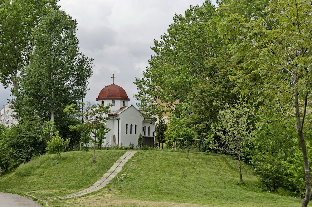 Spring panorama of a part of a residential district neighborhood with a church with modern architecture and belfry, Drujba, Sofia, Bulgaria