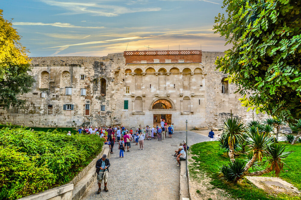 Split, Croatia - Tourists gather in tour groups outside the ancient Golden Gate to the Diocletians Palace section of Old Town Split, Croatia in early autumn.