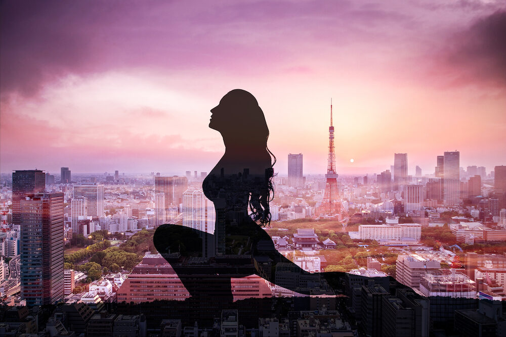 Double exposure of Silhouette yoga woman against the Tokyo city at sunset