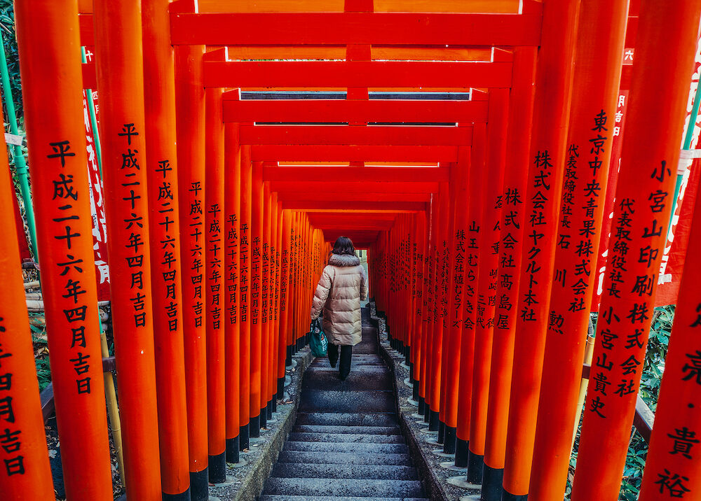 Tokyo Japan - Woman walks down the stairs among wooden pillars of so called Torii path in Shinto Hie Shrine