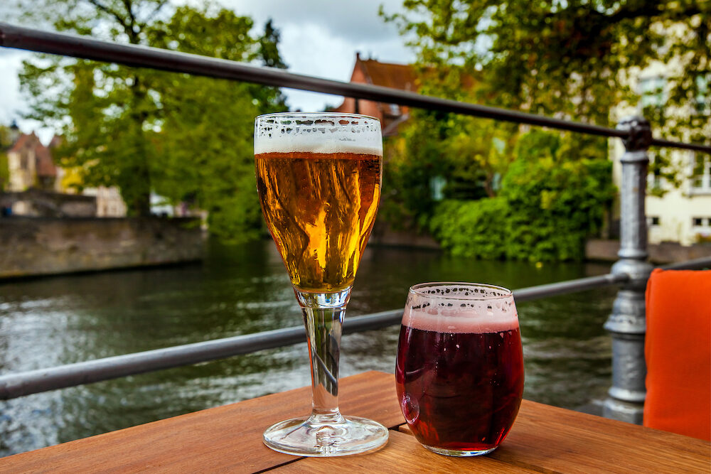 Two glasses of belgian beer standing on the table with Bruges city view