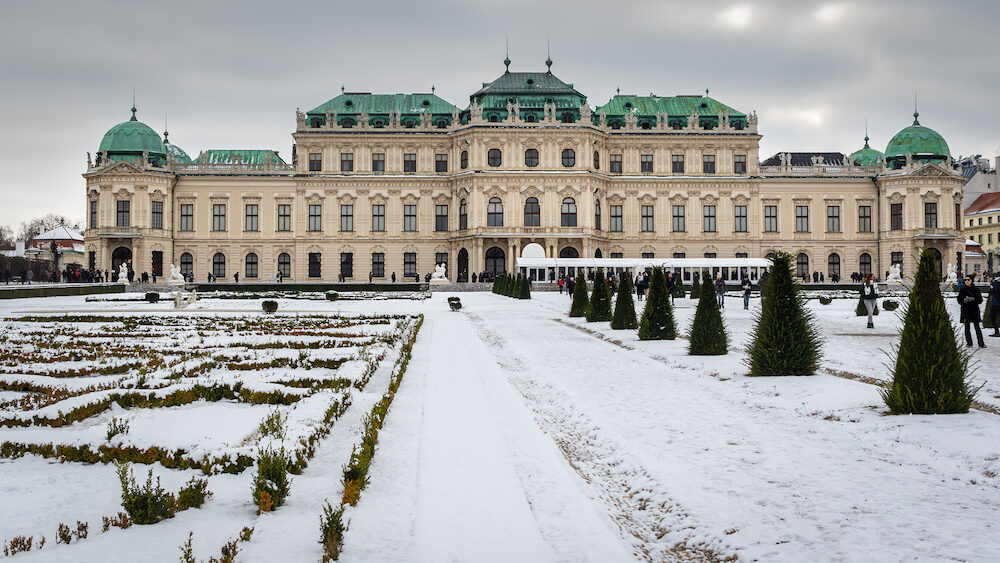 Vienna, Austria - View of famous upper Schloss Belvedere from the palace gardens. Cold winter day, park covered with snow. People and tourists on a walk in the snowy garden
